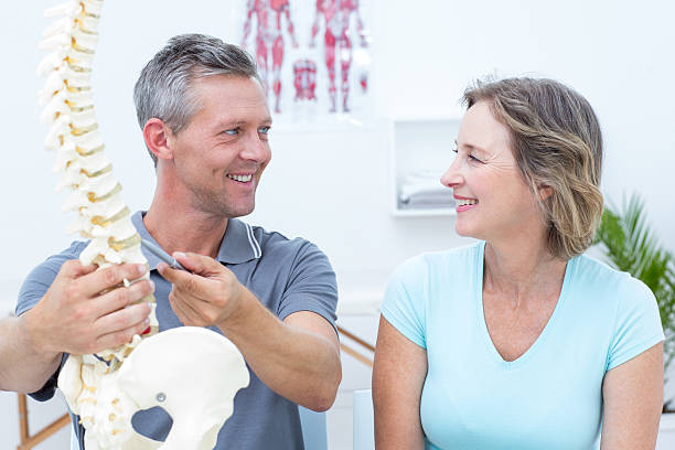 Osteopath showing spine model to his patient in medical office